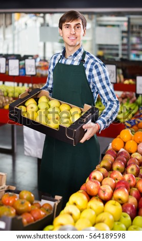 smiling male seller posing with apples, tangerines and bananas in store #564189598