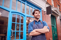 Smiling Male Small Business Owner Wearing Apron Standing Outside Shop On Local High Street