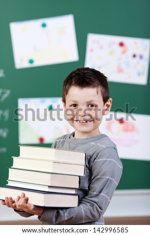 Smiling male student holding a stock of books at the classroom