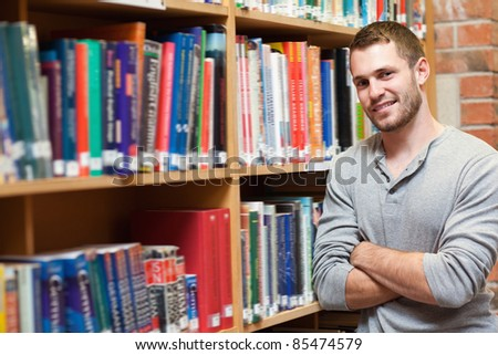 Smiling male student leaning on a shelf in a library