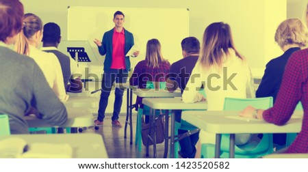 Smiling male teacher giving presentation for students in lecture hall  #1423520582