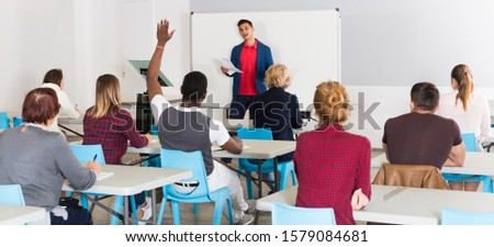Smiling male teacher giving presentation for students in lecture hall  #1579084681