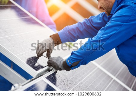 Smiling male technician in blue suit installing photovoltaic blue solar modules with screw. Man electrician panel sun sustainable resources renewable energy source alternative innovation #1029800602