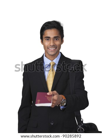 Smiling male traveler with shoulder bag showing his passport in an isolated vertical portrait