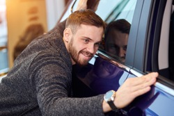 smiling man adores his new modern luxury car. love at first sight, guy checking the polish of the car after mending it. close up photo. you are my baby