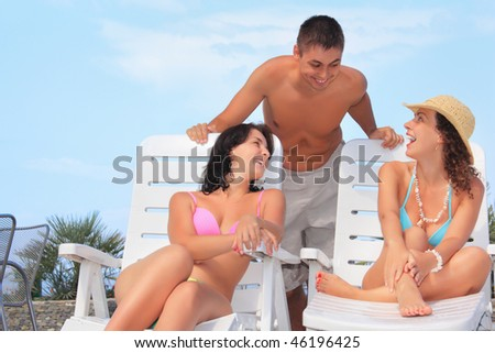 Smiling man and two young women reclining on chaise lounges open-air, Talking with each other