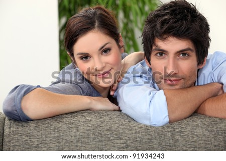 Smiling man and woman leaning on a couch