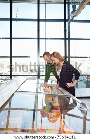 Smiling man and woman looking at a display in a grocery store