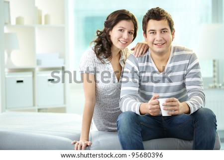 Smiling man and woman sitting together and looking at camera