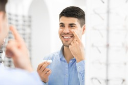 Smiling man applying contacts, looking in mirror, holding contact eye lenses container in hand, copy space