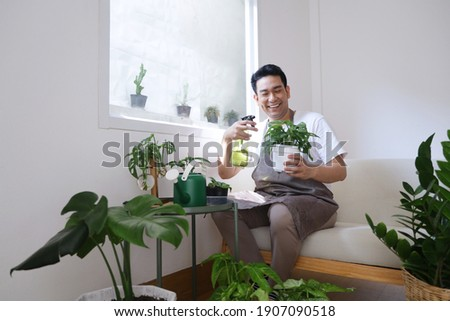 Smiling man Asian in apron sitting on cozy sofa watering plant  in green house. Best Hobby in weekend.