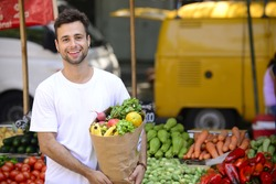 Smiling man carrying a shopping paper bag full of organic fruits and vegetables at an open street market.