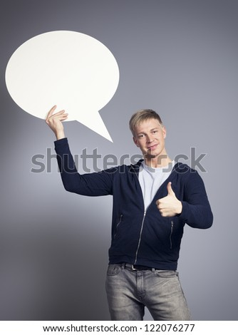 Smiling man giving thumbs up while holding white blank speech balloon with space for text isolated on grey background. - stock photo