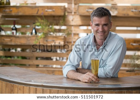 smiling man having a beer in a...