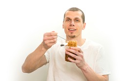 Smiling man hold a fork with fast food noodles in the transparent plastic cup on a white backgound. Happiness. Pasta. Eating. Meal. Hungry. Food. Instant. Happy. Nosh. Excited. Expression