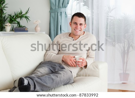 Smiling man holding a cup of coffee in his living room