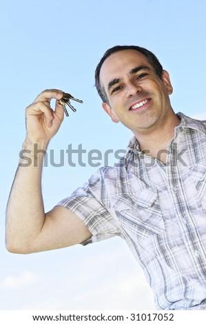 Smiling man holding house keys on blue sky background