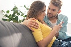 Smiling man hugging depended girlfriend with smartphone on couch
