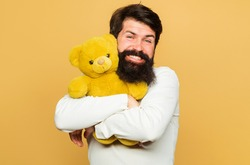 Smiling man hugs Teddy bear. Gift and present. Happy man with plush toy. Birthday Celebration.