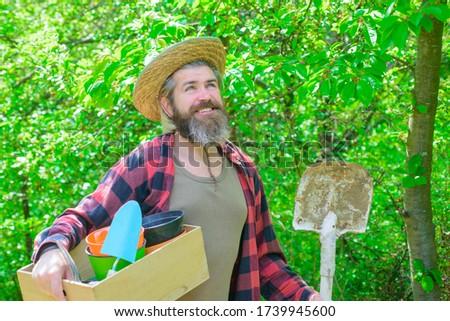 Smiling man in garden. Plants. Garden tools. Gardening. Eco-farm. Work in garden. Bearded man with gardening tools. Work in garden. Gardener work. Farm.
