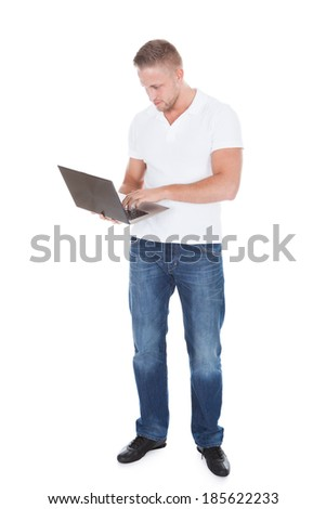 Smiling man in jeans standing using a handheld laptop computer balanced on his palm as he looks at the camera with a friendly smile  isolated on white - stock photo