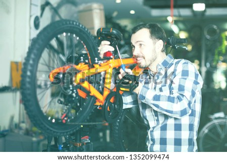 smiling man in sports workshop mounts bike using special tools #1352099474