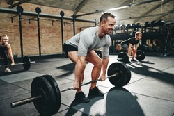 Smiling man in sportswear preparing to lift barbells during a weightlifting class in a gym