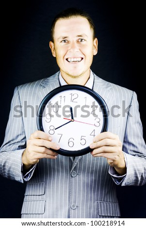 Smiling man in suit, holding clock on black background