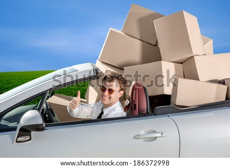 Smiling man in the car with baggage packed in boxes