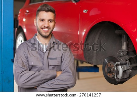 Smiling man in workshop posing with arms crossed against red car at the lift.