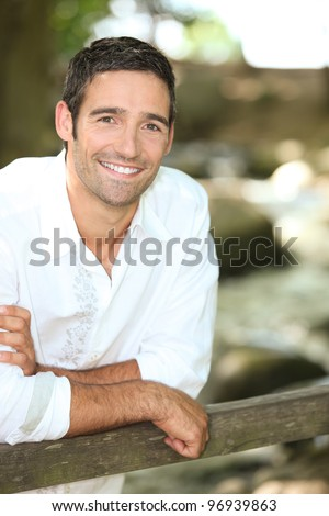 Smiling man leaning on a country gate