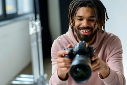 Smiling man looking at camera. Black man in photography studio.
