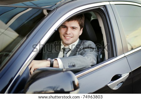 Smiling man looking from a car window