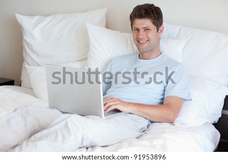 Smiling man lying in bed with his laptop