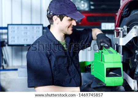 Smiling man mechanic is repairing red car at service station. Repairer in blue jumpsuit and cap is adjusting sensors on wheels. Process of wheels alignment camber check in workshop auto repair shop.
