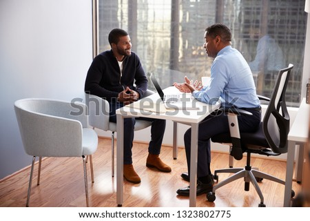 Smiling Man Meeting With Male Financial Advisor Relationship Counsellor In Office