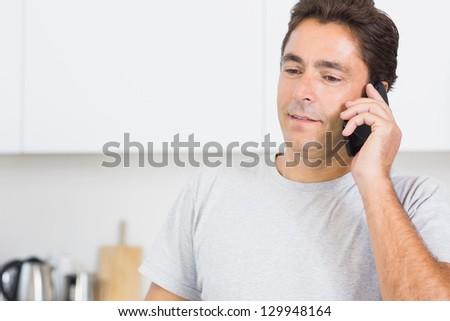 Smiling man phoning in kitchen