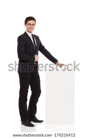 Smiling man presents voting results. Cheerful business man standing and holding bar chart. Full length studio shot isolated on white.