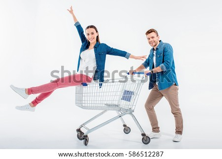 smiling man pushing shopping cart with happy woman sitting on it isolated on white #586512287