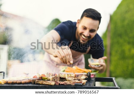 Smiling man seasoning meat on the grill #789016567