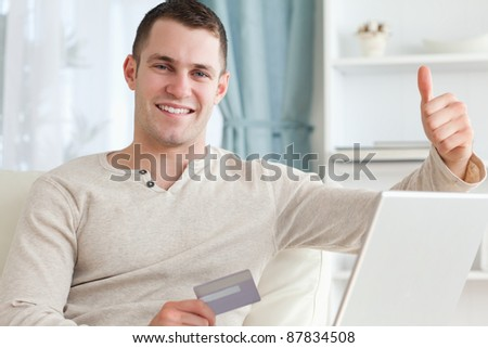 Smiling man shopping online with the thumb up in his living room
