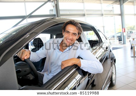 Smiling man sitting at the steering-wheel of brand new car