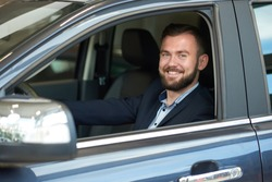 Smiling man sitting in car cabin, looking at camera and smiling. Bearded man holding hand on steering wheel, testing car before purchasing and buying. Customer observing dark blue automobile.