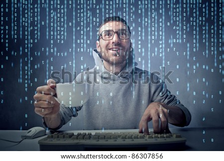 Smiling man sitting in front of a computer screen and holding a cup of coffee