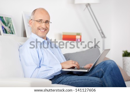Smiling man sitting on the couch and browsing the internet #141127606