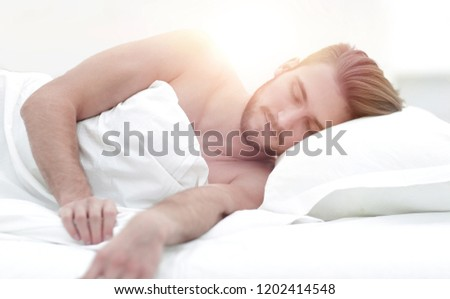 smiling man sleeping on a comfortable bed. #1202414548