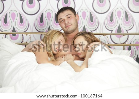 smiling man sleeping with two women in bed