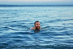 smiling man swims in the sea at dawn.