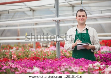 Smiling man taking notes in the greenhouse in garden center