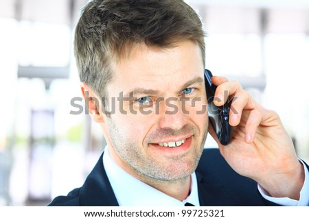 Smiling man using an office phone - stock photo